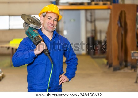Steel construction worker posing with an angle grinder - stock photo