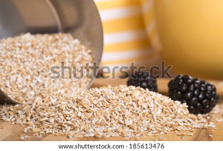 Steel cut oats spilling out of a measuring cup with fresh blackberries - stock photo