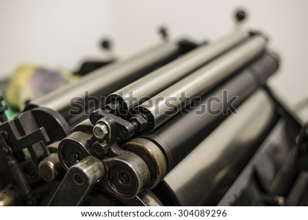 steel cylinders of an old press in a printing shop - stock photo
