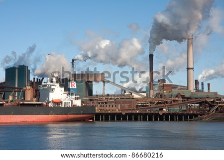 Steel factory with smokestacks and a big cargo ship in front of it - stock photo