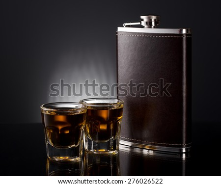 Steel flask and two baby shots of alcohol - stock photo