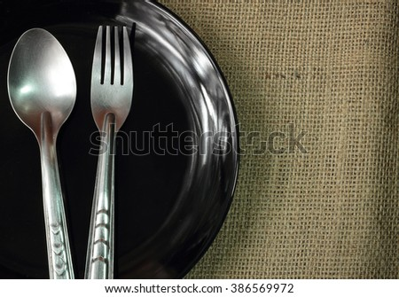 steel fork and spoon on a black ceramic saucer isolated on fabric. Fork and spoon on ceramic saucer some parts. - stock photo