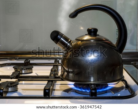 steel Kettle boils and releases steam on a gas stove - stock photo