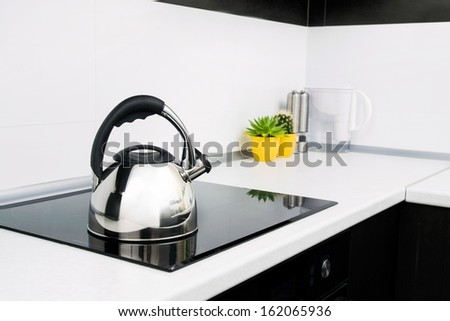 Steel kettle in modern kitchen with induction stove  - stock photo