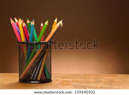 Steel mesh Color pencil pot on the wooden table - stock photo