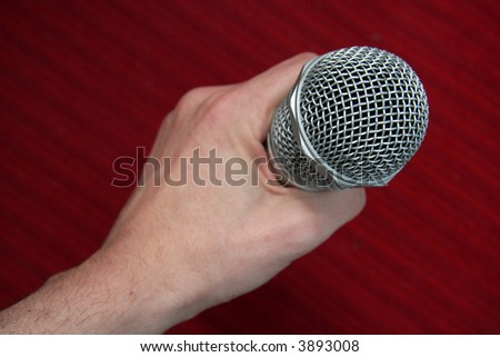 steel microphone in man hand, red background