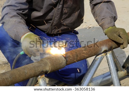 Steel pipe welding operation, closeup of photo