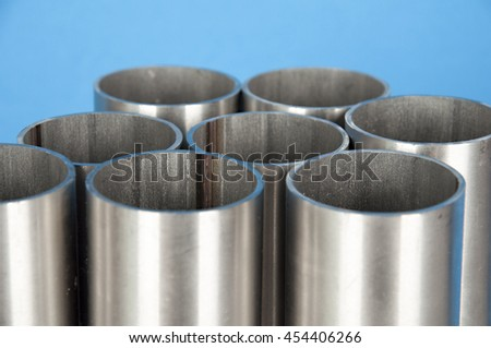 steel pipes on blue background - stock photo