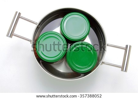 Steel pot with three jars inside boiling in water. Isolated on white background - stock photo