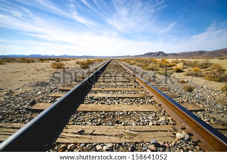 Steel railroad tracks lead into the distance of California's Mojave Desert. - stock photo