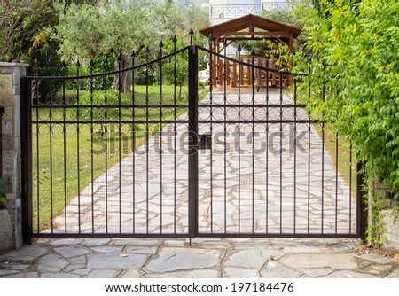Steel security gates protecting house - stock photo