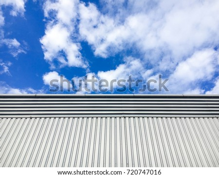 Steel sheet wall of building in factory zone have blue sky with white clouds background.