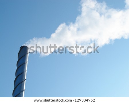Steel smoking stack of the modern boiler-house against a blue sky