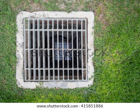 Steel square shape sewer grate on lawn - stock photo