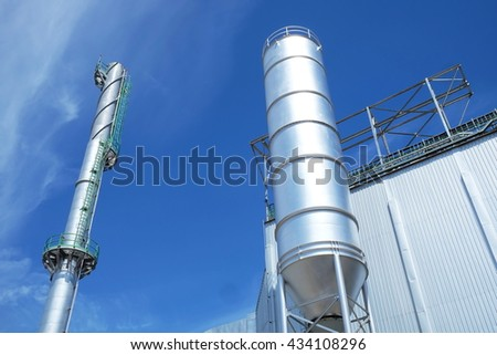Steel tank/silo and industrial smokestack with blue cloud sky background.