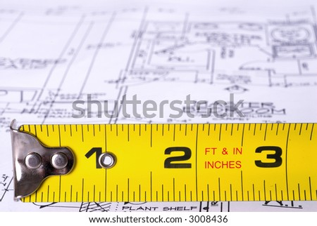 Steel Tape Measure in Front of Blueprints - stock photo