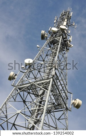 Steel telecommunication tower with antennas over blue sky - stock photo