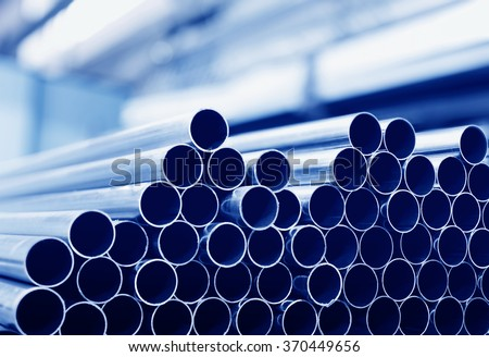 Steel tubes against industrial blurred background - stock photo
