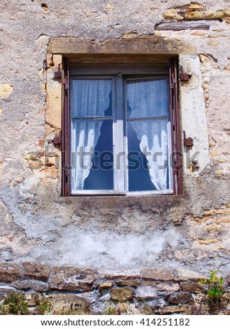 Steel window in a crumbling and patched stone built wall in Burgundy, France