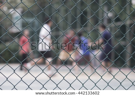 Steel wire mesh fence with People playing basketball court blur background.