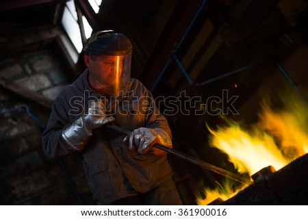 Steel worker in protective clothing raking furnace in an industrial foundry - stock photo