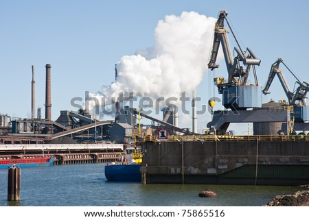 Steelfactory in the Netherlands with cranes loading ships in the harbor - stock photo