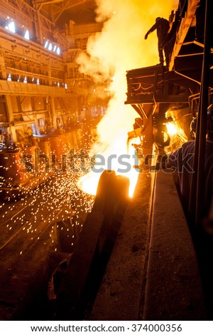 Steelworker near the tanks with hot metal - stock photo