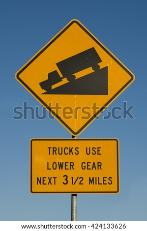 steep hill trucks use lower gear road sign with blue sky background