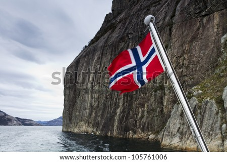 steep mountain over fjord with flag in foreground