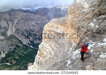 "Steep mountain route and woman climber along via ferrata ""Lipella"", Tofana massif, Dolomite Alps, Italy - stock photo"