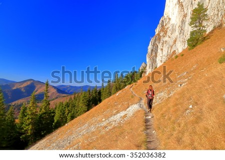 Steep mountain side and woman hiker departing on narrow trail  - stock photo