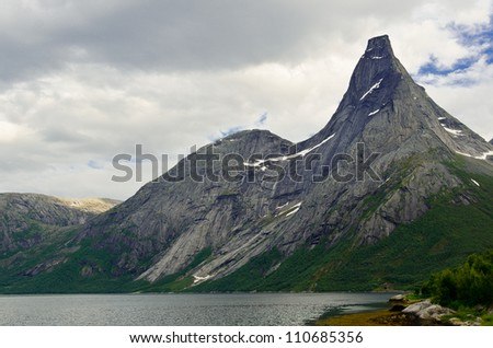Steep peak in northern Norway with the fjord at the bottom - stock photo