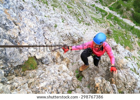 "Steep rock face along via ferrata ""Brigata Tridentina"" and climber woman holding the steel cable, Sella massif, Dolomite Alps, Italy - stock photo"