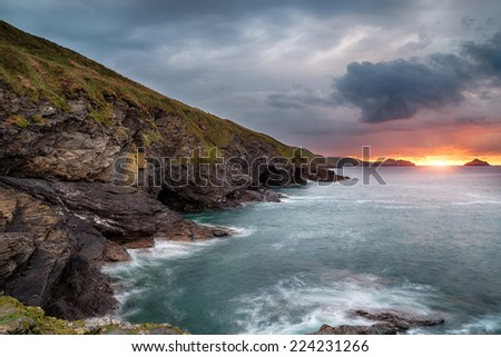 Steep rugged cliffs, sea caves and high waves at Epphaven a small rocky cove between Lundy Bay and Port Quin in Cornwall - stock photo