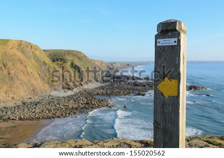 Steeple Point coastal path marker and Duckpool beach near Bude in Cornwall England - stock photo