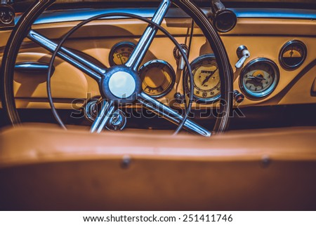Steering wheel and dashboard in interior of old retro automobile. Processed by vintage or retro effect filter - stock photo