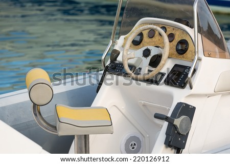 Steering wheel, captain's chair and navigation instruments on a boat cabin - stock photo