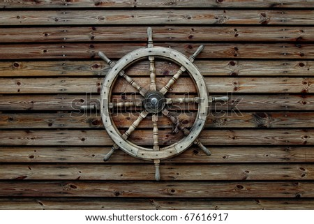 Steering wheel of the ship on a wooden wall of the old house - stock photo