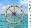 Steering wheel of the ship on the blue sea background - stock photo