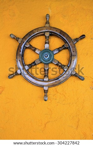 Steering wheel of the ship on yellow stucco wall, Greece - stock photo