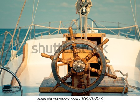 Steering wheel on the old sailboat. Sea voyage of the sailing vessel. Travel at sail boat with a wooden helm in front. Ship wheel on the old yacht - nautical equipment closeup. - stock photo