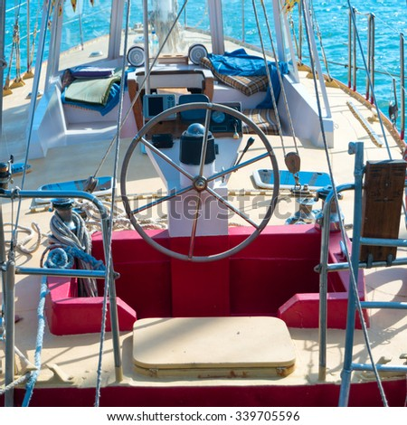 Steering wheel on the yacht with blue sea water background - stock photo