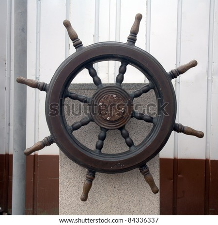 Steering wheel with wooden yacht - stock photo