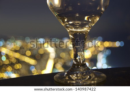 Stem of drink glass in front of city skyline bokeh