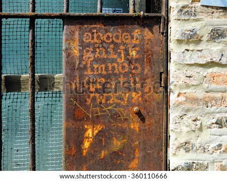 Stenciled alphabet rusting away on metal gate - stock photo