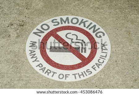 Stenciled no smoking sign in public and city walkways,parks, and pedestrian path / No Smoking / Permanent stenciled signs with striking highlight warning in red - stock photo