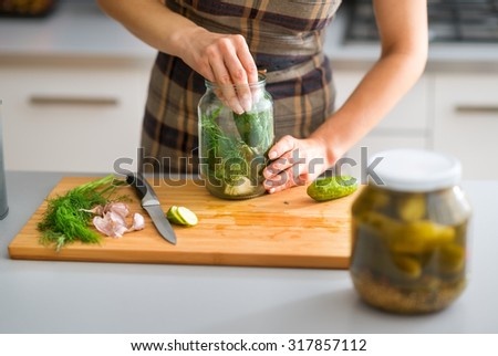 Step by step, the flavors come together. Here, a woman's hands are hard at work, stuffing cucumbers and dill into a pickling jar as she prepares home-made dill pickles. - stock photo