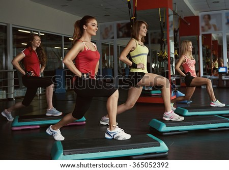 Step course in the gym. Group of female doing aerobics fitness for losing weight. - stock photo