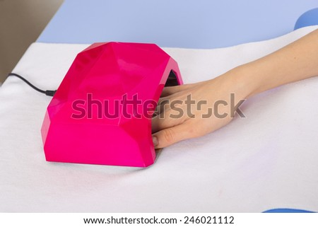 step of manicure process: nail gel polish drying in manicure lamp