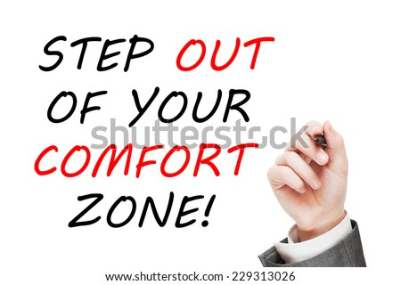 Step out of your comfort zone! Man writing a motivational message on white background - stock photo